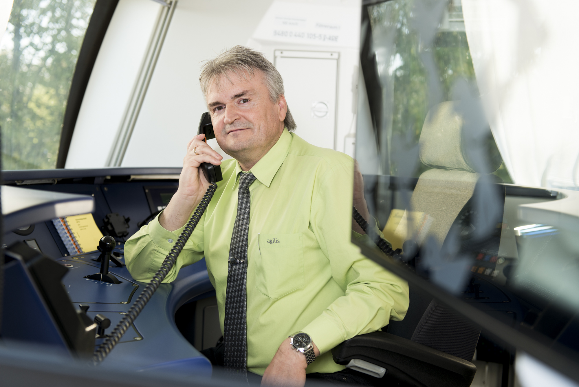 Ein Triebfahrzeugführer sitzt im Führerstand eines agilis-Zuges.