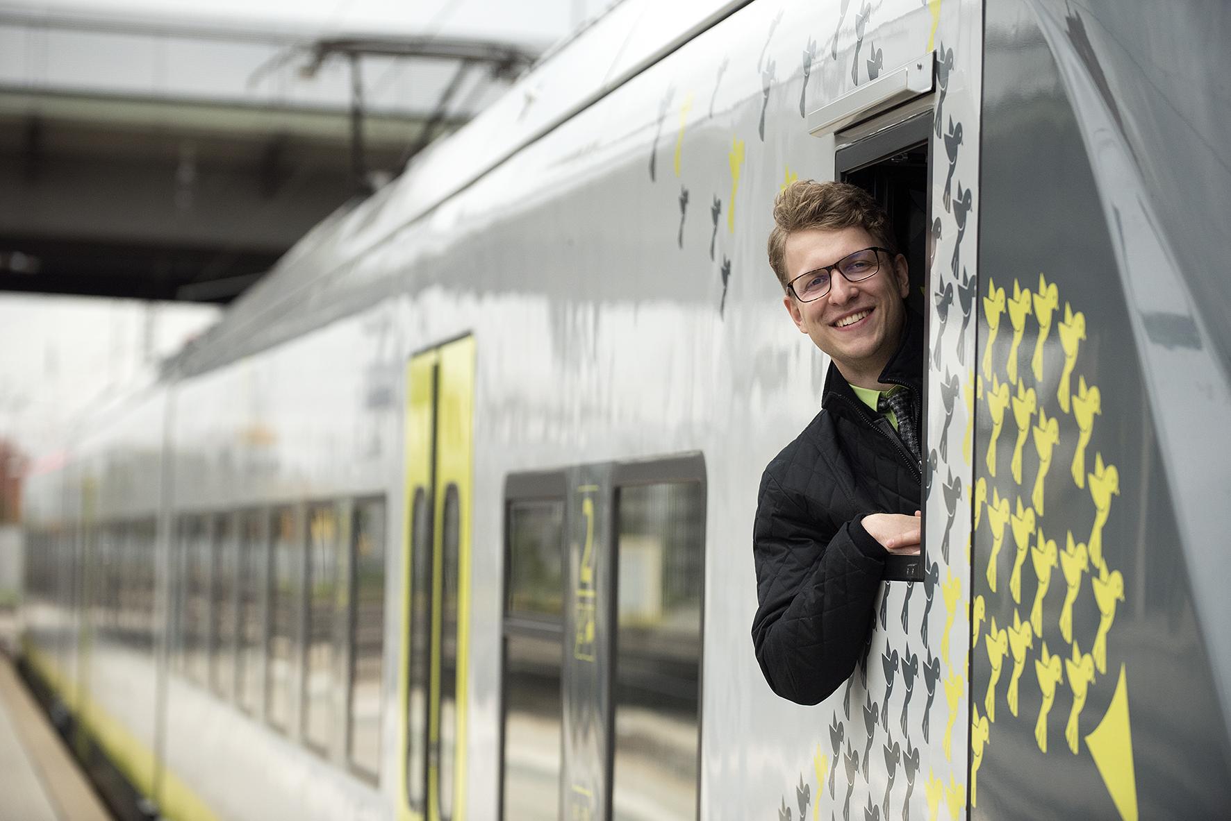 Ein Triebfahrzeugführer von agilis blickt aus dem Führerstand des Zuges und lacht.